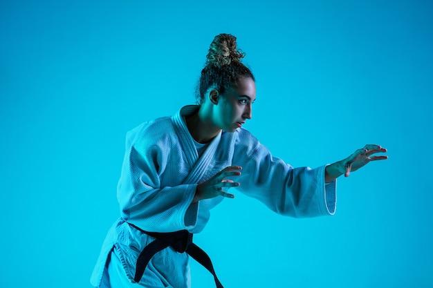 Judoist femminile professionista in posa isolato su sfondo blu studio in neon