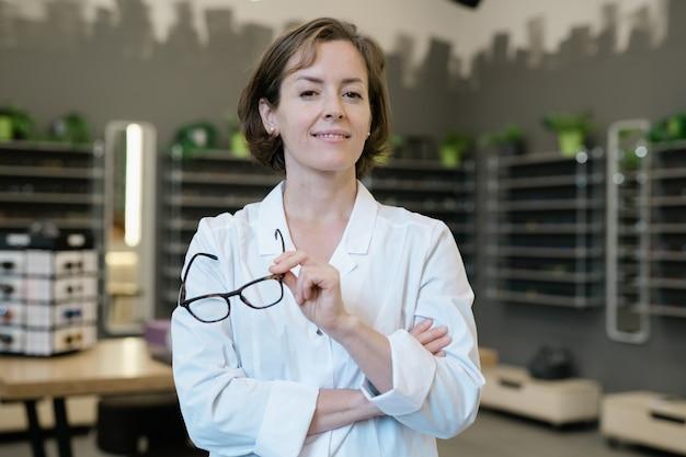 All'ottico optometrista femminile professionale in whitecoat che tiene un paio di occhiali nuovi nell'ambiente del negozio di ottica