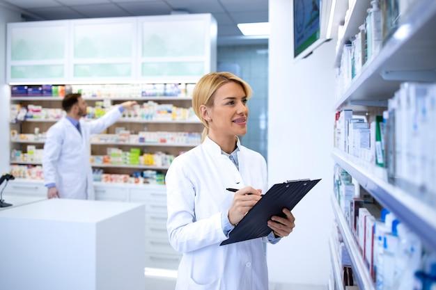 Farmacista femminile professionista in camice bianco che lavora al negozio di farmacia prendendo appunti sui farmaci sullo scaffale.