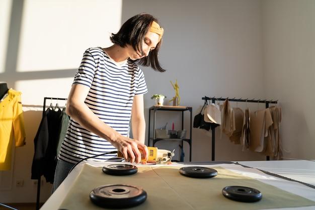 La fogna femminile professionale realizza campioni di abbigliamento in studio con taglierina elettrica sul tavolo in officina