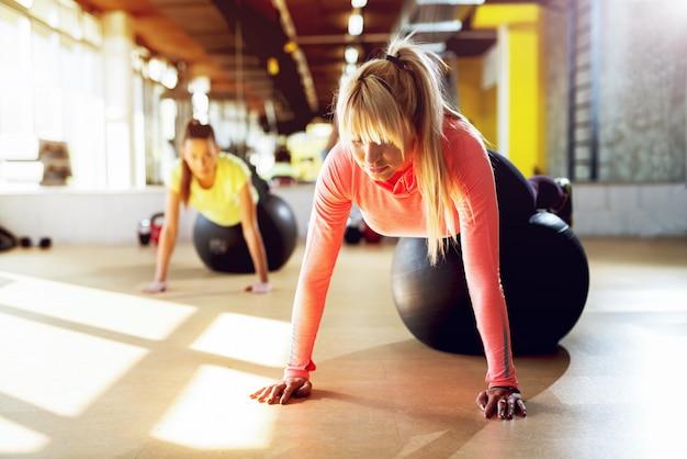 L'istruttore femminile professionista al lavoro della palestra spinge aumenta con la palla dei pilates.