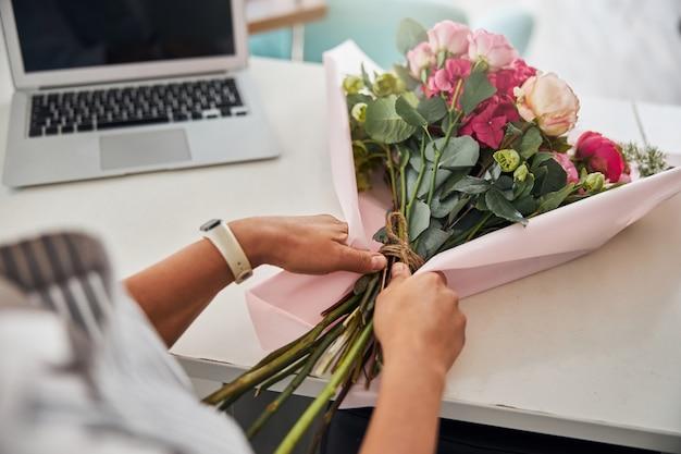 Finitura fiorista professionista che crea un bellissimo bouquet