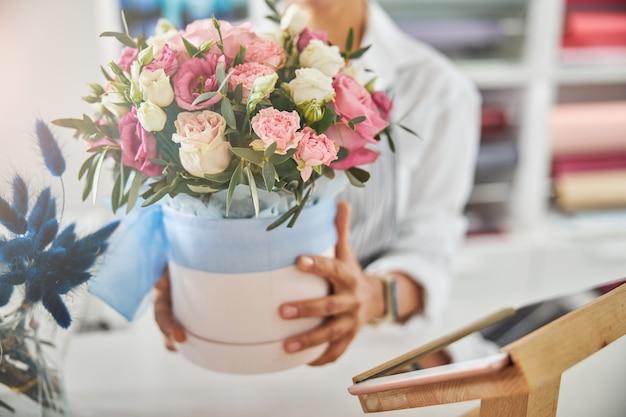 Fiorista professionista che mostra un vaso di fiori con rose
