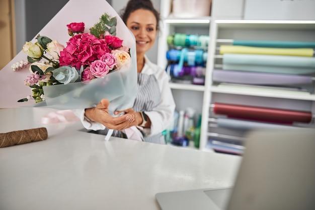 Assistente di negozio di fiori professionista con in mano un bellissimo bouquet