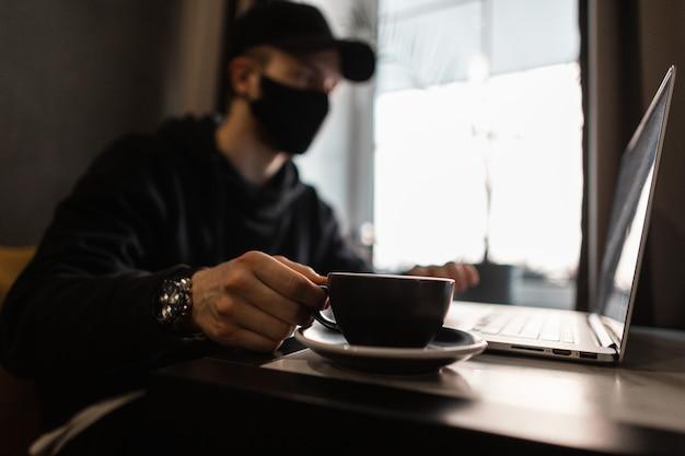 Uomo libero professionista con maschera medica nera in berretto alla moda e felpa con cappuccio con orologio di lusso che beve caffè e lavora al computer portatile al bar