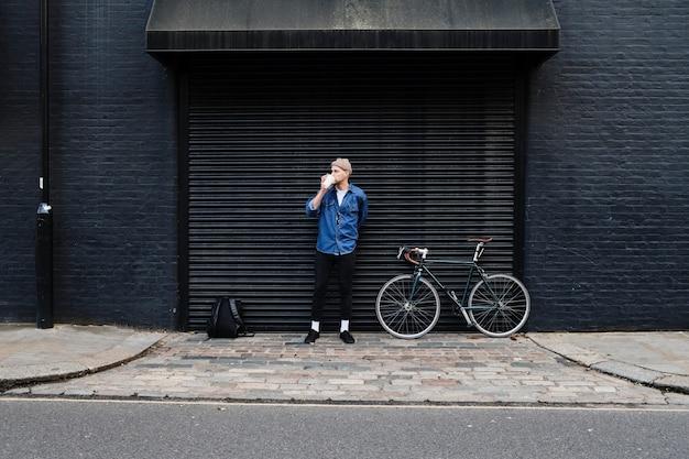 Libero professionista giovane uomo in piedi con la sua bici e bere caffè fuori davanti a una casa nera.
