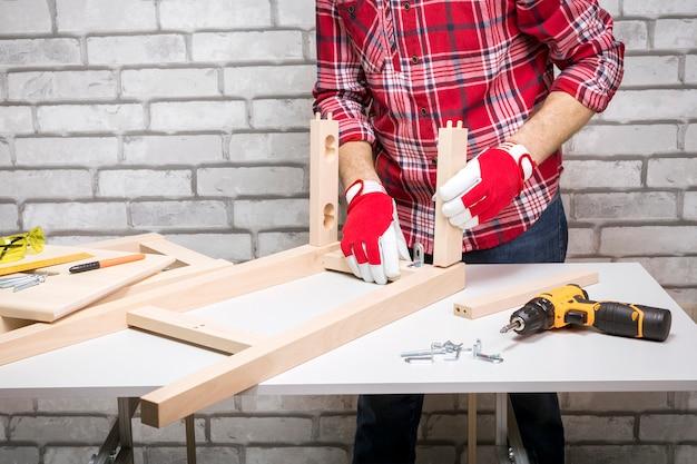 L'addetto all'assemblaggio di mobili professionale assembla la sedia. installazione di mobili.