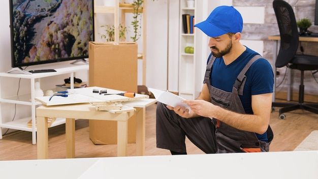 Operaio professionista dell'assemblaggio di mobili che controlla la posizione dello scaffale. il lavoratore segue le istruzioni.