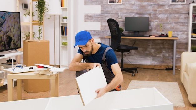Lavoratore professionista dell'assemblaggio di mobili che indossa un berretto mentre monta uno scaffale nella nuova casa.