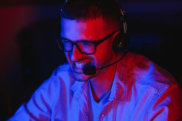 Il giocatore professionista gioca al videogioco sul suo computer. sta partecipando al torneo di giochi informatici online o all'internet cafe. indossa gli occhiali e parla al microfono.
