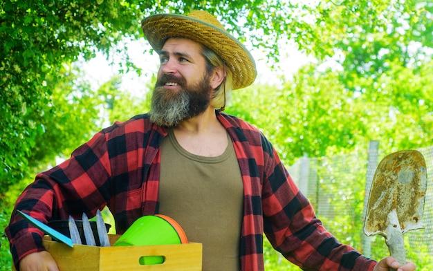 Giardiniere professionista. uomo barbuto con attrezzi da giardinaggio. lavoro in giardino.