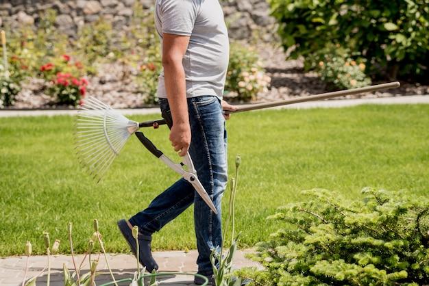 Il giardiniere professionista va a tagliare alberi con forbici da giardino e rastrello. progettazione del paesaggio. giardinaggio