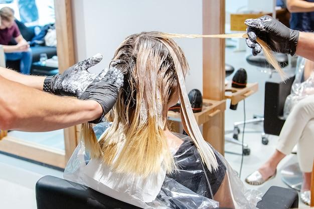 Colorazione professionale dei capelli per le donne in salone, stile luminoso e alla moda.