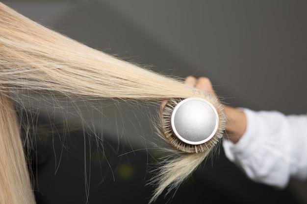 Parrucchiere professionista che asciuga i capelli biondi della donna con una spazzola pettine e un asciugacapelli