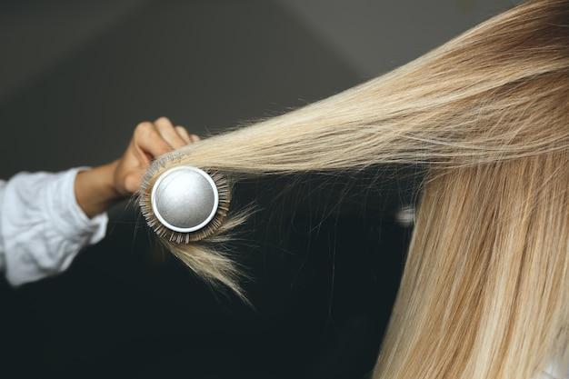 L'hair stylist professionista raddrizza i capelli del cliente con una spazzola pettine e un asciugacapelli