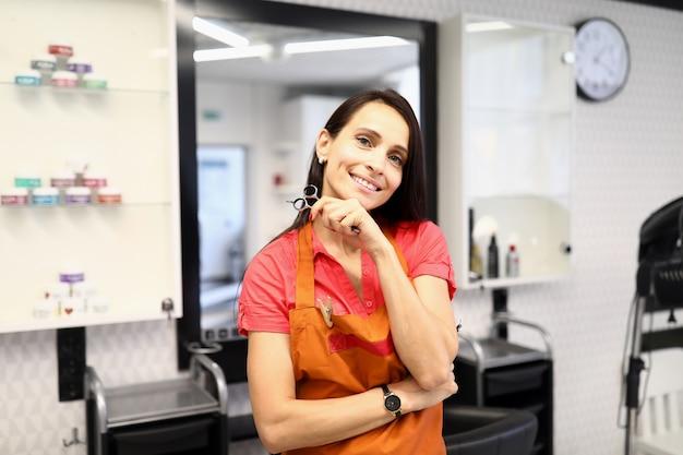 Parrucchiere professionista tenere le forbici in mano nel salone di bellezza.
