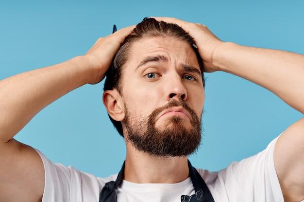 Uomo parrucchiere professionista in un grembiule grigio si fa i capelli su una parete blu e le forbici pettine.