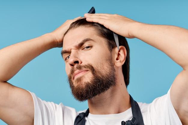Uomo di parrucchiere professionista in grembiule grigio che fa i capelli su sfondo blu e vista ritagliata.