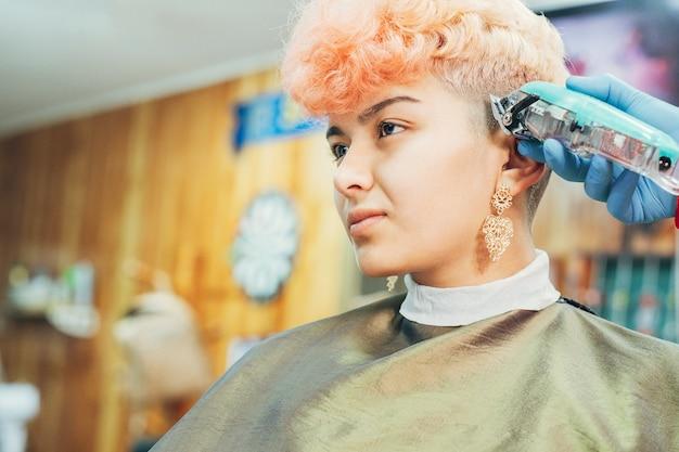 Mani del parrucchiere professionista che tagliano i capelli di una donna con i capelli rosa corti e tinti
