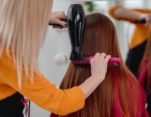 Parrucchiere professionista rafforza i capelli lunghi della ragazza modello utilizzando asciugacapelli e spazzola