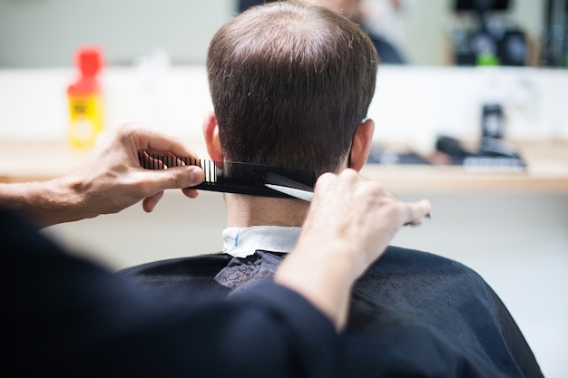 Un parrucchiere professionista che indossa una maschera protettiva che taglia i capelli a un cliente durante il coronavirus