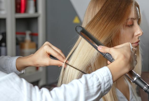 Parrucchiere professionista raddrizza i capelli con la piastra per capelli