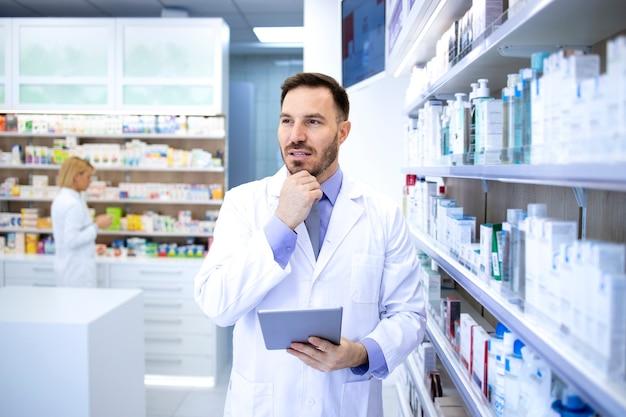 Farmacista maschio bello professionista in camice bianco che tiene compressa e pensa in farmacia o in farmacia.