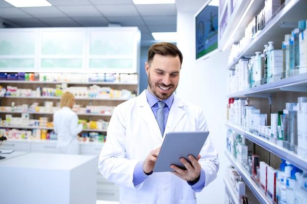 Farmacista maschio bello professionista che lavora in farmacia o in farmacia e controlla i farmaci sul suo tablet.