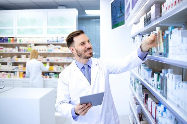 Farmacista maschio bello professionista che lavora in farmacia o in farmacia e prende farmaci dallo scaffale.