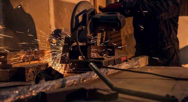 Uomo laborioso professionista che taglia o che macina la superficie di metallo sulla macchina della smerigliatrice e scintille alla fabbrica di industria di lavorazione dei metalli