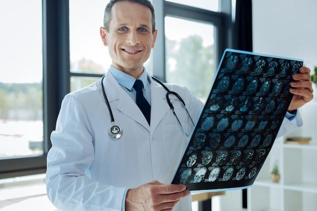 Assistenza sanitaria professionale. bello neurologo maschio esperto in piedi nel suo ufficio e studiando un elettroencefalogramma mentre cerca una diagnosi medica