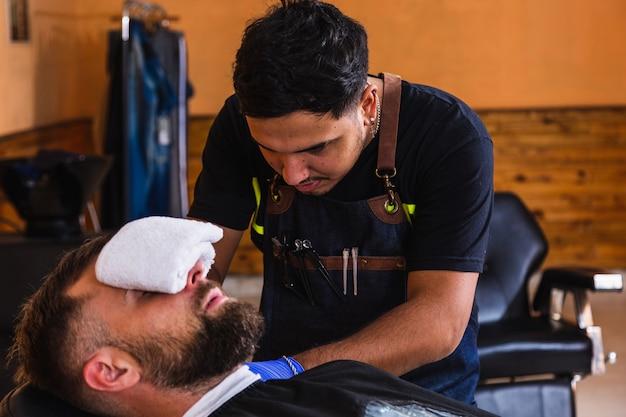 Barbiere professionista hipster che taglia la barba di un cliente nel salone.