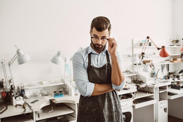 Professionista della sua attività. ritratto di gioielliere maschio fiducioso che indossa grembiule e occhiali di regolazione mentre si trova in studio di creazione di gioielli