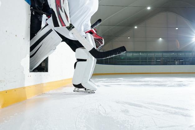 Giocatore di hockey professionista in uniforme, casco protettivo, guanti e pattini che escono dalla tribuna alla pista di pattinaggio per giocare allo stadio mentre si tiene il bastone