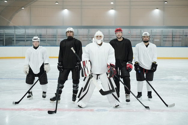 Giocatori di hockey professionisti e il loro allenatore in divisa sportiva, guanti, pattini e caschi protettivi in piedi sulla pista di pattinaggio mentre aspettano il gioco