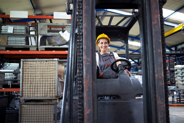 Autista industriale professionale che opera macchina del carrello elevatore nel magazzino della fabbrica