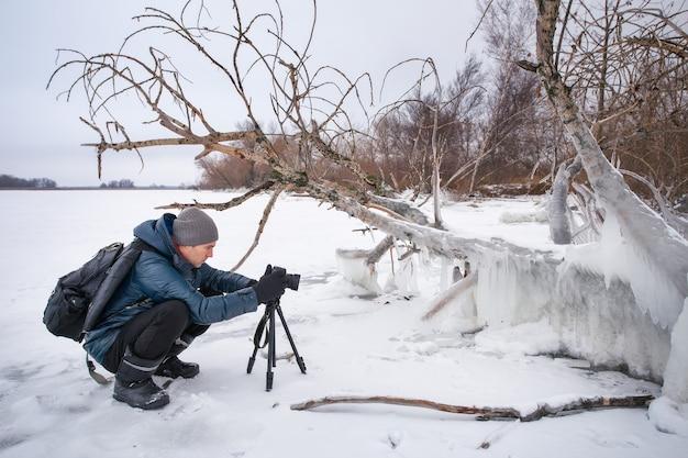 Professionista sul lago. il fotografo naturalista scatta foto con la fotocamera a specchio sul fiume nella stagione invernale.