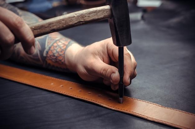 Il pellettiere professionista taglia i prodotti in pelle nel suo negozio di concia