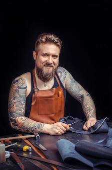 Leather worker professionista che taglia i contorni della pelle per la sua nuova produzione sul posto di lavoro