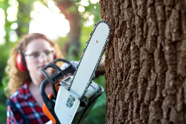 Boscaiolo professionista nella foresta che taglia un tronco di quercia con la motosega.