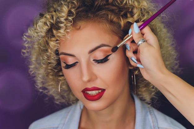 Make-up artist professionista che fa trucco modello glamour