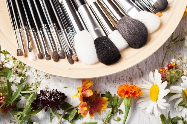 Pennelli professionali per il trucco sul piatto accanto a fiori selvatici su fondo di legno