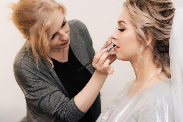 Truccatore professionista dipinge le labbra di una giovane ragazza con il rossetto in uno studio di bellezza