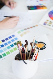 Corsi di trucco professionale. ritagliato colpo artista pittura sul posto di lavoro. primo piano della tazza di ceramica bianca delle spazzole e delle matite.