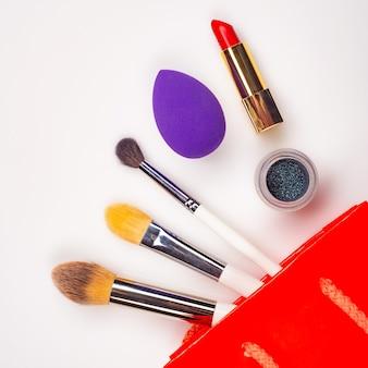 Trucco professionale su sfondo bianco. pennelli, rossetto e altri prodotti, un piatto con spazio per le copie