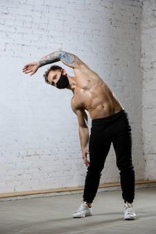 Atleta professionista maschio formazione su sfondo muro di mattoni indossando maschera facciale.