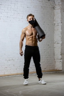 Atleta professionista maschio allenamento su sfondo muro di mattoni indossando maschera facciale