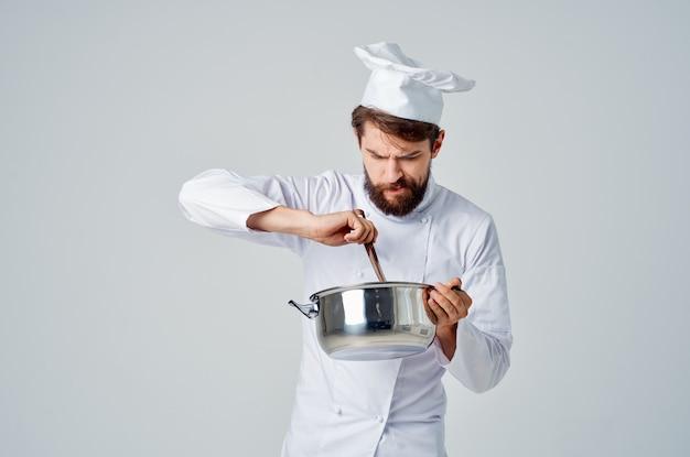 Lo chef professionista maschio con una casseruola in mano assaggia il ristorante di cibo