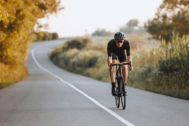 Ciclista maschio professionista in casco nero, occhiali protettivi e activewear in modo dinamico in bicicletta su strada asfaltata con sfocatura dello sfondo.