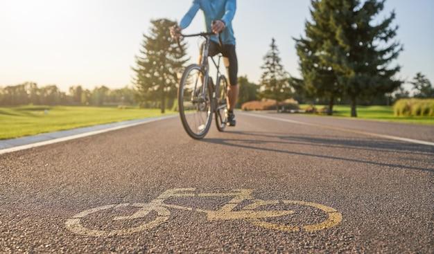 Ciclista professionista maschio in sella a una bici da strada su una pista ciclabile sullo sfondo.